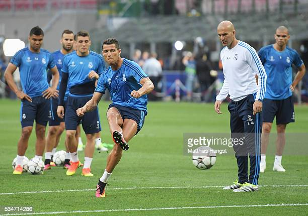 Cristiano Ronaldo of Real Madrid has a shot as Head coach Zinedine Zidane looks on during a Real Madrid training session on the eve of the UEFA...