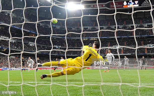Cristiano Ronaldo of Real Madrid has his penalty kick saved by Sergio Rico of Sevilla FC to score Real's 2nd goal during the La Liga match between...