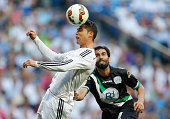 Cristiano Ronaldo of Real Madrid heads the ball under pressure from Angel Crespo of Cordoba during the La Liga match between Real Madrid CF and...