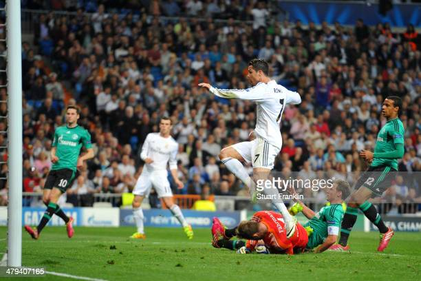 Cristiano Ronaldo of Real Madrid hurdles goalkeeper Ralf Fahrmann of Schalke as he scores the opening goal during the UEFA Champions League Round of...