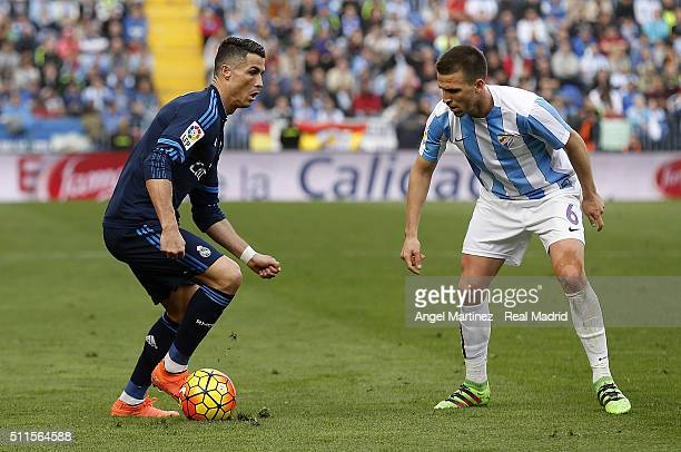 Cristiano Ronaldo of Real Madrid is challenged by Ignacio Camacho of Malaga CF during the La Liga match between Malaga CF and Real Madrid CF at La...