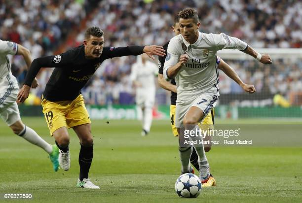 Cristiano Ronaldo of Real Madrid is challenged by Lucas Hernandez of Club Atletico de Madrid during the UEFA Champions League Semi Final first leg...