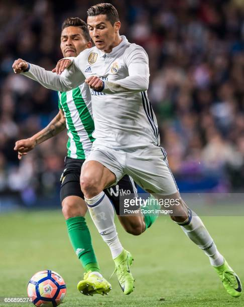 Cristiano Ronaldo of Real Madrid is challenged by Petros Matheus dos Santos Araujo of Real Betis during their La Liga match between Real Madrid and...