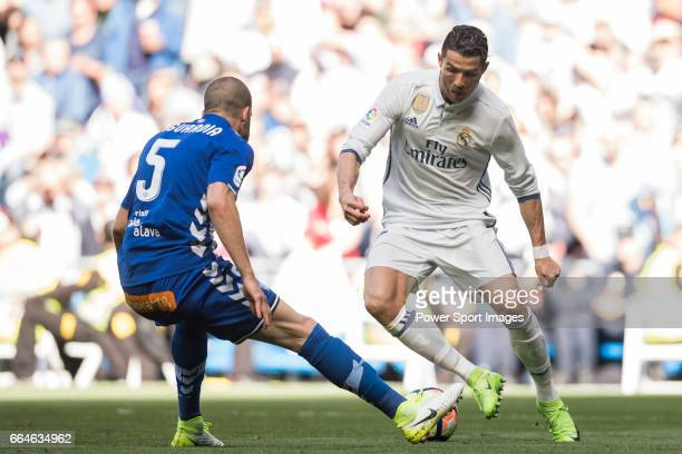 Cristiano Ronaldo of Real Madrid is challenged by Victor Laguardia Cisneros of Deportivo Alaves during their La Liga match between Real Madrid and...
