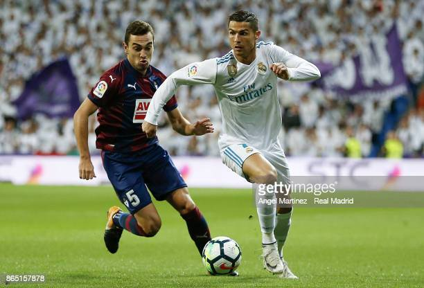 Cristiano Ronaldo of Real Madrid is chased by Gonzalo Escalante of Eibar during the La Liga match between Real Madrid and Eibar at Estadio Santiago...