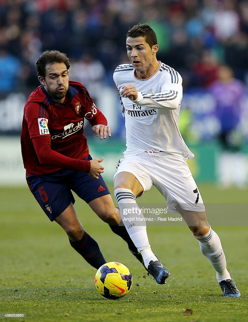 Cristiano Ronaldo of Real Madrid is chased by Lolo Ortiz of CA Osasuna during the La Liga match between CA Osasuna and Real Madrid at Estadio Reyno de Navarra on December 14, 2013 in Pamplona, Spain.