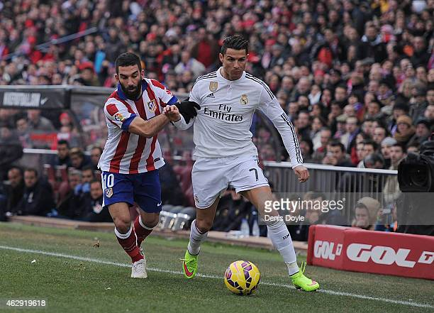 Cristiano Ronaldo of Real Madrid is tackled by Arda Turan of Club Atletico de Madrid during the La Liga match between Club Atletico de Madrid and...