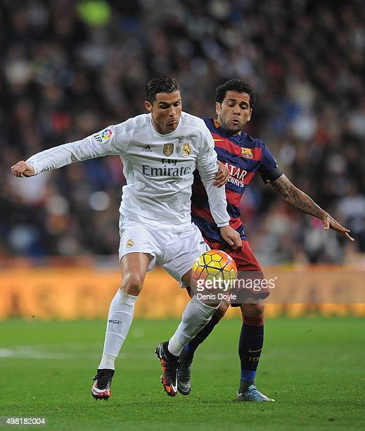 Cristiano Ronaldo of Real Madrid is tackled by Daniel Alves of FC Barcelona during the La Liga match between Real Madrid and Barcelona at Estadio...