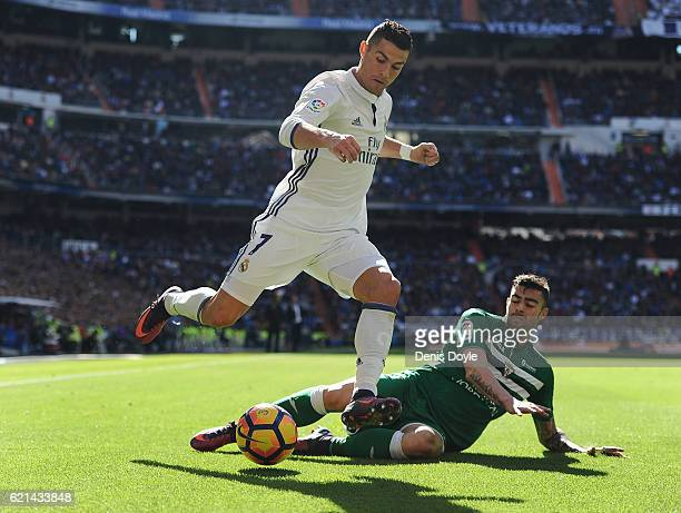 Cristiano Ronaldo of Real Madrid is tackled by Diego Rico of CD Leganes controls the ball while being challenged by during the Liga match between...