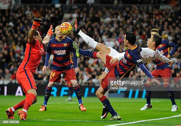 Cristiano Ronaldo of Real Madrid is tackled by Sergio Busquets of FC Barcelona during the La Liga match between Real Madrid and Barcelona at Estadio...
