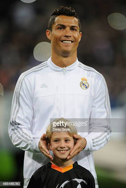 Cristiano Ronaldo of Real Madrid jokes with a player escort during the UEFA Champions League Group A match between Real Madrid CF and Paris...