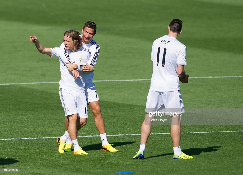 <a gi-track='captionPersonalityLinkClicked' href=/galleries/search?phrase=Cristiano+Ronaldo+-+Soccer+Player&family=editorial&specificpeople=162689 ng-click='$event.stopPropagation()'>Cristiano Ronaldo</a> (C) of Real Madrid jokes with teammate <a gi-track='captionPersonalityLinkClicked' href=/galleries/search?phrase=Luka+Modric&family=editorial&specificpeople=560350 ng-click='$event.stopPropagation()'>Luka Modric</a> (L) while Real's new signing <a gi-track='captionPersonalityLinkClicked' href=/galleries/search?phrase=Gareth+Bale&family=editorial&specificpeople=609290 ng-click='$event.stopPropagation()'>Gareth Bale</a> looks on during a team training session on September 13, 2013 in Madrid, Spain.