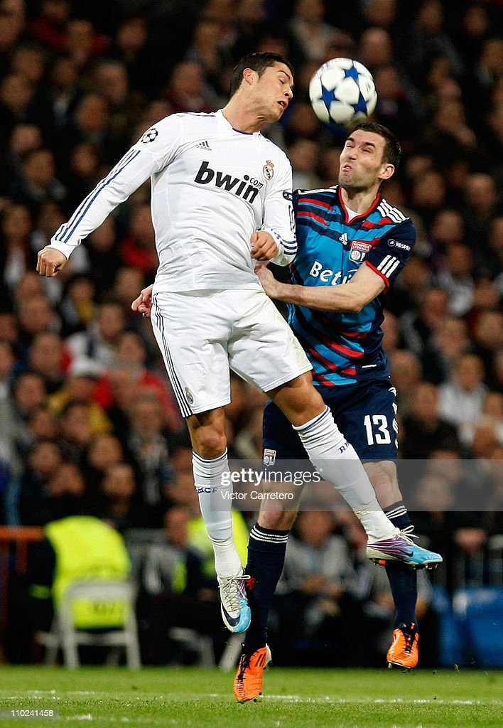<a gi-track='captionPersonalityLinkClicked' href=/galleries/search?phrase=Cristiano+Ronaldo&family=editorial&specificpeople=162689 ng-click='$event.stopPropagation()'>Cristiano Ronaldo</a> of Real Madrid jumps for a high ball with Anthony Reveillere of Lyon during the UEFA Champions League round of 16 second leg match between Real Madrid and Lyon at Estadio Santiago Bernabeu on March 16, 2011 in Madrid, Spain.