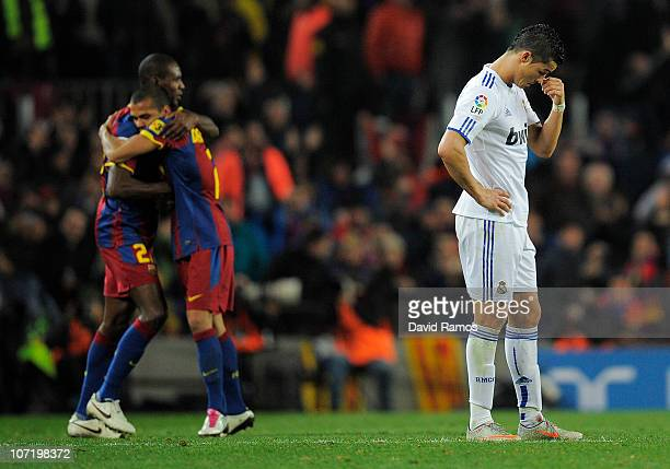 Cristiano Ronaldo of Real Madrid looks down as Eric Abidal and Dani Alves of Barcelona celebrates the fifth goal against Real Madrid during the La...
