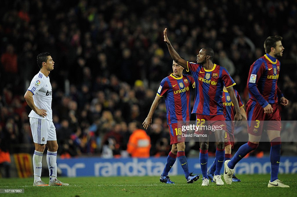 Cristiano Ronaldo of Real Madrid (L) looks on as Eric Abidal (2ndR) of Barcelona gestures after Barcelona scored five goals againts Real Madrid, during the La Liga match between Barcelona and Real Madrid at the Camp Nou Stadium on November 29, 2010 in Barcelona, Spain.