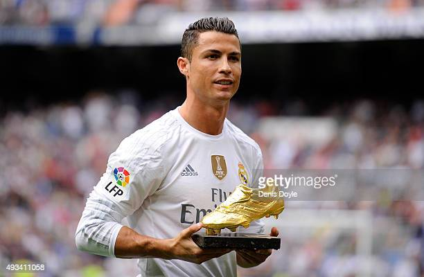 Cristiano Ronaldo of Real Madrid looks on with his Golden Shoe award during the La Liga match between Real Madrid CF and Levante UD at estadio...