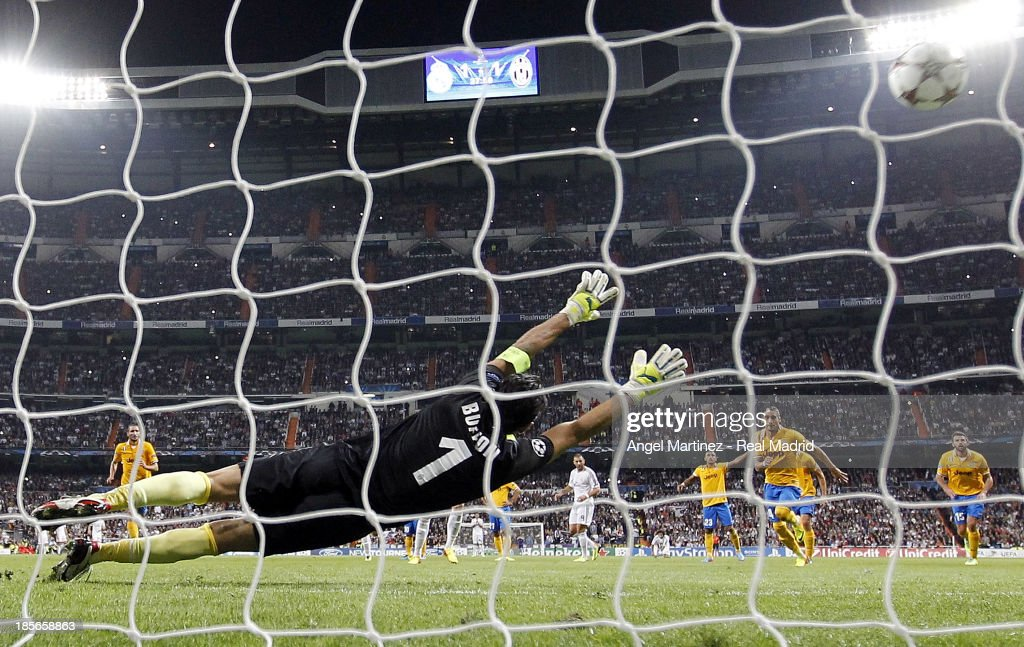 Cristiano Ronaldo of Real Madrid scores from the penalty spot his team's second goal past Gianluigi Buffon of Juventus during the UEFA Champions League Group B match between Real Madrid and Juventus at Estadio Santiago Bernabeu on October 23, 2013 in Madrid, Spain.