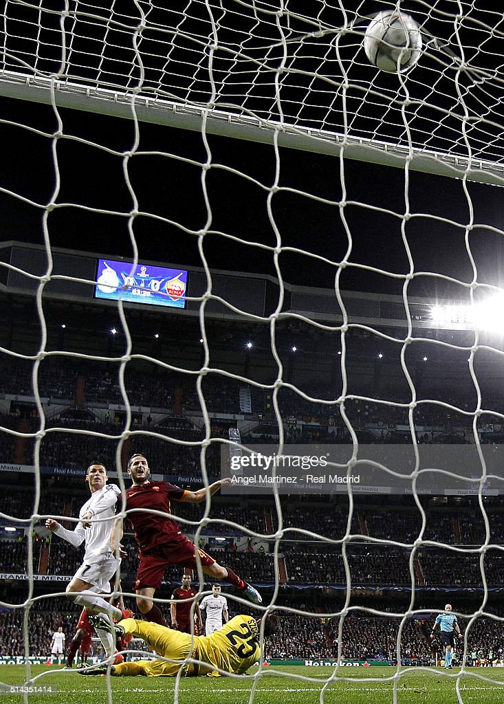 Cristiano Ronaldo of Real Madrid scores the opening goal past Kostas Manolas (R) and Wojciech Szczesny of AS Roma during the UEFA Champions League Round of 16 Second Leg match between Real Madrid CF and AS Roma at Estadio Santiago Bernabeu on March 8, 2016 in Madrid, Spain.