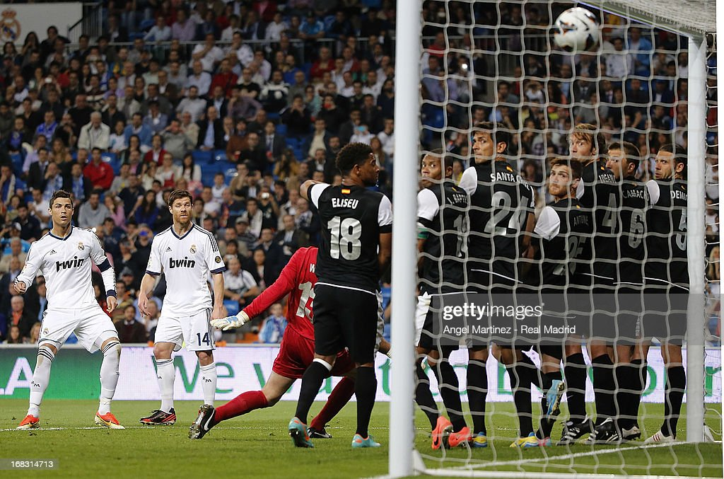 <a gi-track='captionPersonalityLinkClicked' href=/galleries/search?phrase=Cristiano+Ronaldo+-+Soccer+Player&family=editorial&specificpeople=162689 ng-click='$event.stopPropagation()'>Cristiano Ronaldo</a> (L) of Real Madrid scores the second goal goal from a free kick during the La Liga match between Real Madrid and Malaga at Estadio Santiago Bernabeu on May 8, 2013 in Madrid, Spain.