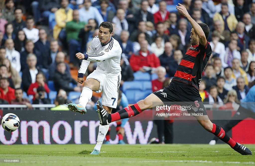 <a gi-track='captionPersonalityLinkClicked' href=/galleries/search?phrase=Cristiano+Ronaldo+-+Soccer+Player&family=editorial&specificpeople=162689 ng-click='$event.stopPropagation()'>Cristiano Ronaldo</a> of Real Madrid shoots on goal past Andres Tunez of Celta de Vigo during the La Liga match between Real Madrid and Celta de Vigo at Bernabeu on October 20, 2012 in Madrid, Spain.