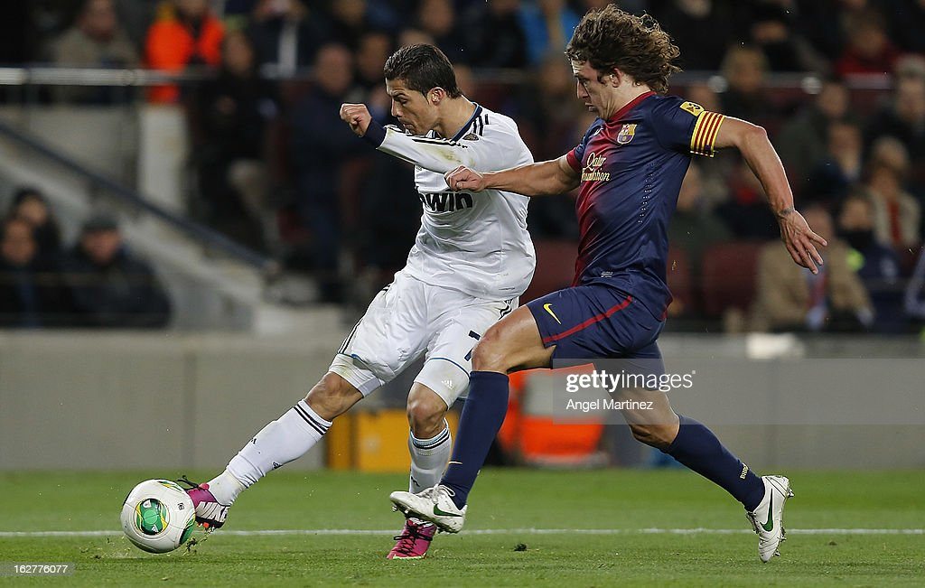 Cristiano Ronaldo of Real Madrid shoots on goal under pressure from Carles Puyol of Barcelona during the Copa del Rey semi final second leg match between FC Barcelona and Real Madrid CF at Camp Nou on February 26, 2013 in Barcelona, Spain.