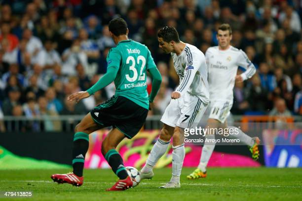 Cristiano Ronaldo of Real Madrid shoots past Joel Matip of Schalke to score his team's second goal during the UEFA Champions League Round of 16...