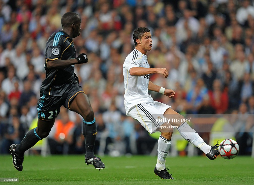 <a gi-track='captionPersonalityLinkClicked' href=/galleries/search?phrase=Cristiano+Ronaldo+-+Soccer+Player&family=editorial&specificpeople=162689 ng-click='$event.stopPropagation()'>Cristiano Ronaldo</a> (R) of Real Madrid strikes to score the opening goal past <a gi-track='captionPersonalityLinkClicked' href=/galleries/search?phrase=Souleymane+Diawara&family=editorial&specificpeople=695613 ng-click='$event.stopPropagation()'>Souleymane Diawara</a> of Marseille during the Champions League group C match between Real Madrid and Marseille at the Estadio Santiago Bernabeu on September 30, 2009 in Madrid, Spain.