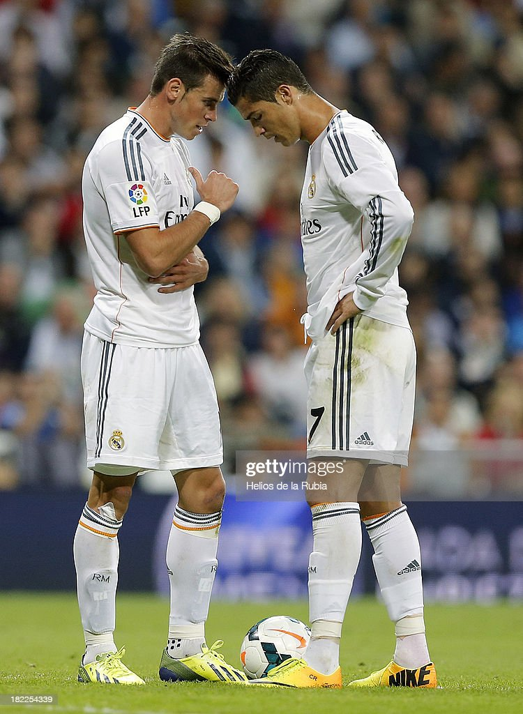 Cristiano Ronaldo (R) of Real Madrid talks with his teammate Gareth Bale during the La Liga match between Real Madrid and Club Atletico de Madrid at Estadio Santiago Bernabeu on September 28, 2013 in Madrid, Spain.