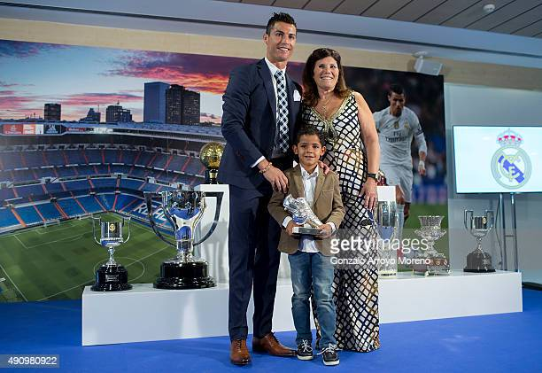 Cristiano Ronaldo poses for a picture with his trophy as alltime top scorer of Real Madrid CF held by his son Cristiano Ronald JR and his mother...