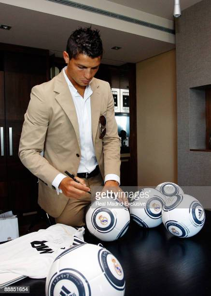 Cristiano Ronaldo signs a football balls of Real Madrid before his official presentation as new Real Madrid Player at the Mirasierra Hotel on July 6...