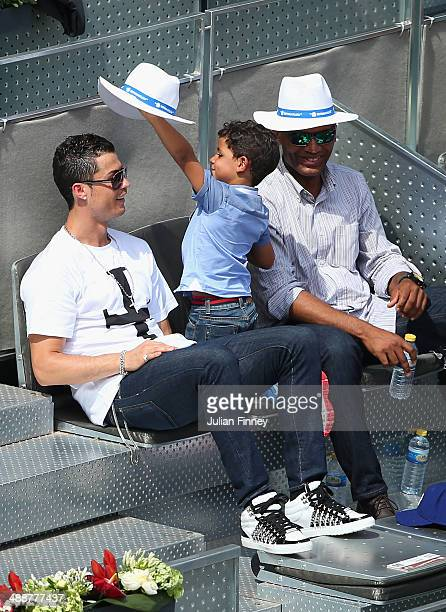 Cristiano Ronaldo with Cristiano Ronaldo Jnr as they watch Rafael Nadal of Spain play against Jarkko Nieminen of Finland during day six of the Mutua...