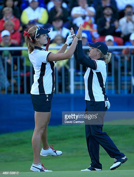 Cristie Kerr of the United States races to celebrate with Lexi Thompson after Thompson had holed a birdie putt on the 15th hole against Azahara Munoz...