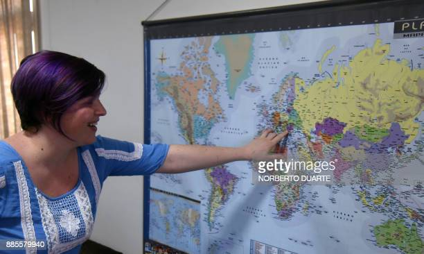 Cristina Bitiuska a Romanian musician living in Paraguay points out her country on a map during an interview with AFP in Asuncion on November 30 2017...