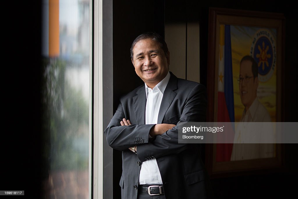 Cristino Naguiat, chairman of the Philippine Amusement & Gaming Corp., poses for a photograph next to a portrait of President Benigno Aquino in Manila, the Philippines, on Tuesday, Jan. 15, 2013. Annual revenue from gaming may rise to $10 billion in 2017 once Manila's Entertainment City is fully operational, Naguiat said. Photographer: Julian Abram Wainwright/Bloomberg via Getty Images