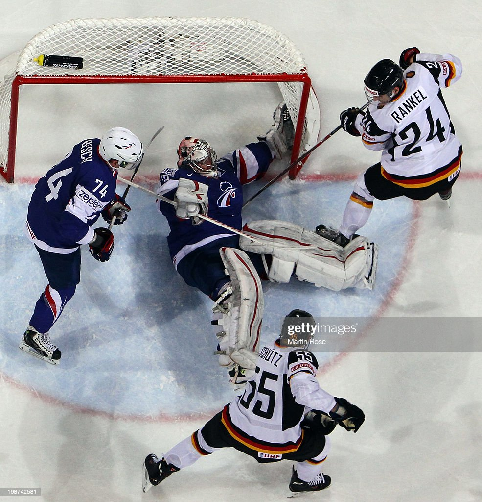 Cristobal Huet (C), goaltender of France makes a save on Felix Schuetz (#55) of Germany during the IIHF World Championship group H match between France and Germany at Hartwall Areena on May 14, 2013 in Helsinki, Finland.