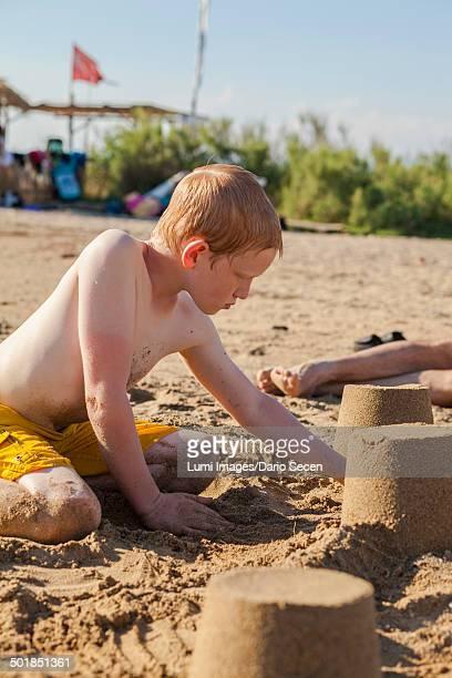 Croatia, Dalmatia, Boy On Beach Building Sandcastle