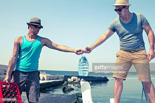 Croatia, Dalmatia, Young men at the seaside, transporting beer