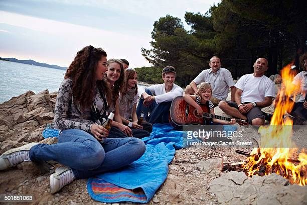 Croatia, Group Of People Sitting Around Campfire