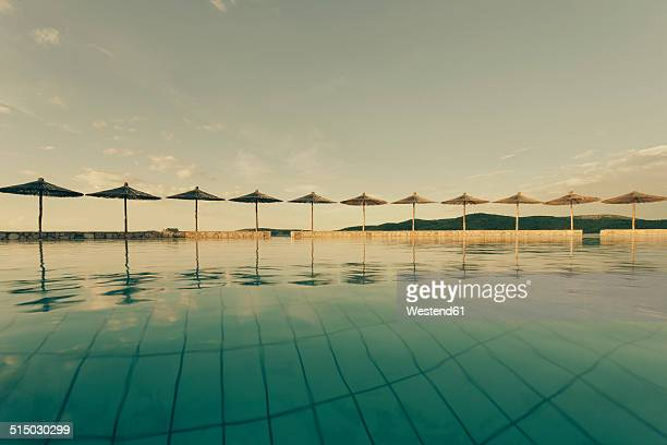 Croatia, Sibenik, Sunshades, Swimming pool of a hotel facility, Evening mood