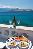 Croatia, Table laid with food in restaurant, adriatic sea in background at Baska