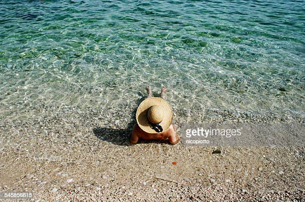 Croatia, Woman with straw hat sunbathing