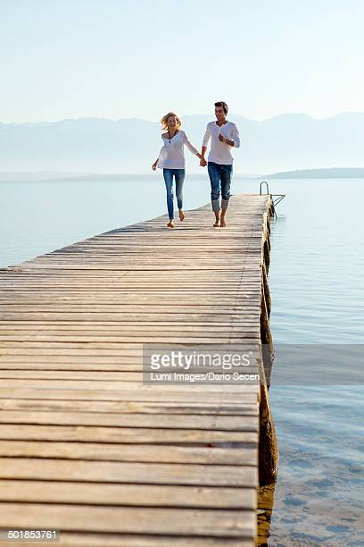 Croatia, Young couple holding hands on boardwalk