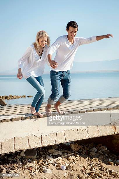 Croatia, Young couple jumping on beach
