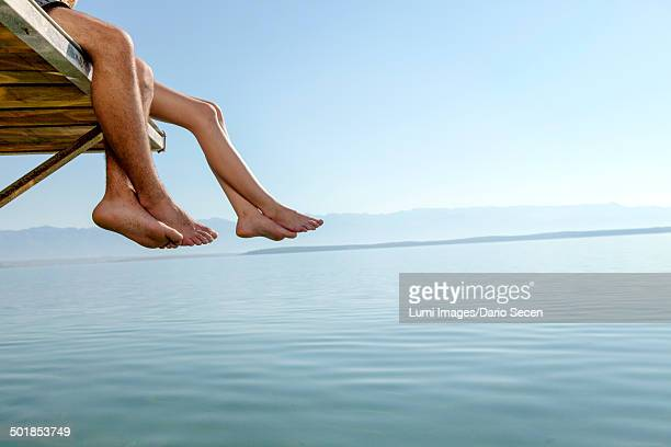 Croatia, Young couple relaxes on jetty, by the sea