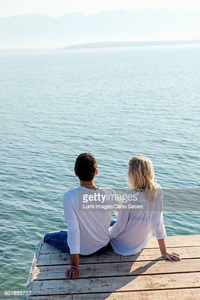 Croatia, Young couple sits on boardwalk, rear view, by the sea