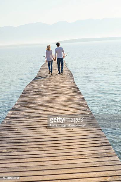 Croatia, Young couple walks across boardwalk, rear view