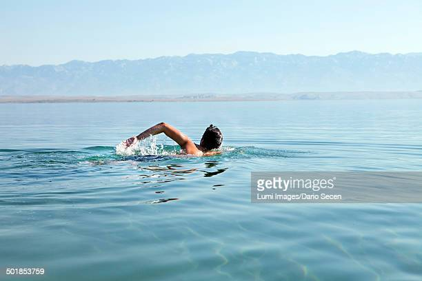 Croatia, Young man swims in the Adriatic Sea