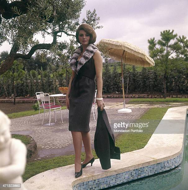 Croatian actress Sylva Koscina posing by the swimming pool in a fur necked sheath 1964