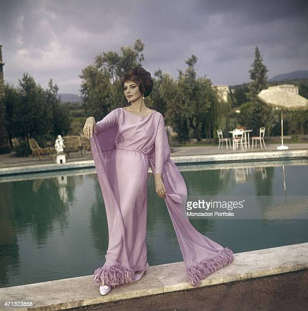 Croatian actress Sylva Koscina posing by the swimming pool in evening dress 1964