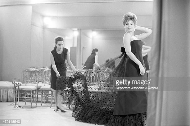'Croatian actress Sylva Koscina trying on an evening dress at Italian tailor Roberto Capucci's atelier while an assistant tidies her rear veil Paris...